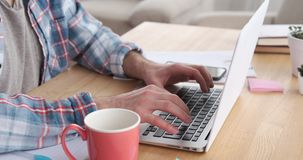 Male hand working on laptop and drinking coffee at home office stock video