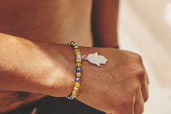 Male Hand Wrist With Colorful Bracelet And Silver Pendant Royalty Free Stock Photo