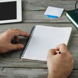 Male hand writes in notebook close up. Male hand writes in a notebook close up Royalty Free Stock Images
