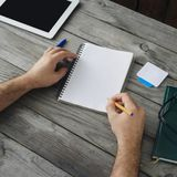 Male hand writes in a notebook close up. Top view Home workplace. Male hand writes in a notebook close up Stock Image