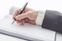 Male hand writing. Closeup of a male hand writing on notepad on a white desk Stock Photo