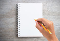 Male hand is writing in a big notepad on wooden table Stock Photography