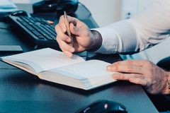 A male hand is writing in a big notepad on a wooden table Royalty Free Stock Photography