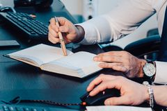 A male hand is writing in a big notepad on a wooden table Royalty Free Stock Photo