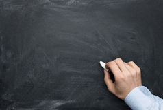 Male hand writing on a blackboard Royalty Free Stock Images