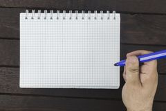 Male hand is writing on blank notepad. On a wooden table Royalty Free Stock Image