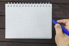 Male hand is writing on blank notepad. On a wooden table Stock Images