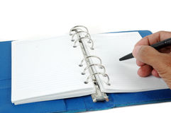 Male hand writing at blue leather notebook Royalty Free Stock Photos