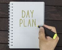 Male hand is writing Day plan on a notepad. On a wooden table Royalty Free Stock Image