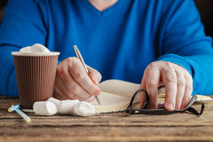 Male hand writing in diary and holding cup of hot chocolate with Stock Image