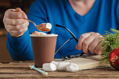 Male hand writing in diary and holding cup of hot chocolate with Royalty Free Stock Photo