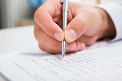 Male hand writing in document Royalty Free Stock Image