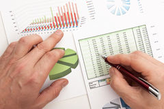 Male hand writing in the document. Male hand is writing in business document lying on the table Stock Images