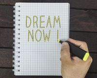 Male hand is writing Dream now on a notepad. On a wooden table royalty free stock image