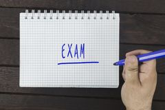 Male hand is writing Exam on a notepad. On a wooden table Stock Image