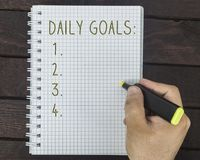 Male hand is writing daily goals on a notepad. On a wooden table Stock Photos