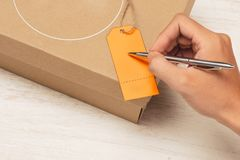 Male hand writing on luggage tag on brown paper parcel Stock Photos