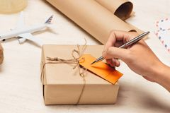 Male hand writing on luggage tag on brown paper parcel.  Royalty Free Stock Image