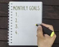 Male hand is writing monthly goals on a notepad. On a wooden table Royalty Free Stock Photography
