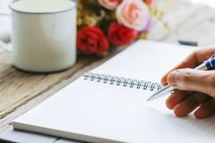Male hand writing in notebook with pen. Close shot of a human hand writing something on the paper on the foreground Stock Photos