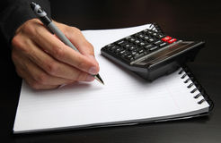 Male hand writing on a notepad. With a pen, and using a calculator Stock Photo
