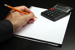 Male hand writing on a notepad. With a pencil, and using a calculator Stock Image