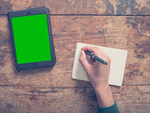 Male hand writing in notepad and using tablet. A male hand is writing in a notepad there is a tablet computer on the table as well with a green screen Royalty Free Stock Image