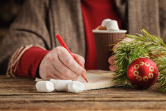 Male hand writing plans for new year in notebook while as he dri Stock Image