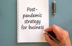 Free Male Hand Writing `post-pandemic Strategy For Business` On White Note,  On Blue Background. Business Concept Stock Images - 186415334