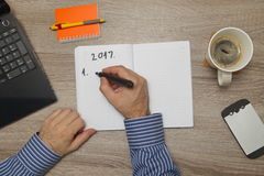 Male hand writing text plans for year 2017. ` in notebook. While as he drinks coffee Stock Image