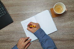 Male hand writing text ` to do` in notebook while as he drinks coffee. Top down Royalty Free Stock Photo
