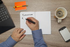 Male hand writing text ` to do` in notebook while as he drinks coffee. Top down view Stock Photos
