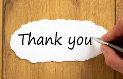 Male hand writing `thank you` on white paper on wooden table. Business concept