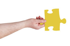 Male hand with yellow puzzle piece Royalty Free Stock Image