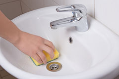Male hand with yellow sponge cleaning sink Royalty Free Stock Photo