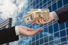 Male Handing Stack of Cash to Woman with Corporate Building. Male Hand Handing Stack of Cash to Woman with Corporate Building Royalty Free Stock Photos