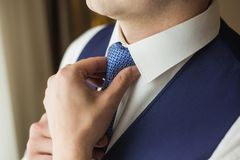 Male hands adjusting blue necktie Stock Photos