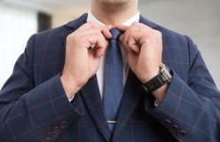 Male hands adjusting blue tie. Male businessman hands adjusting blue tie as luxury expensive man clothing Stock Photography