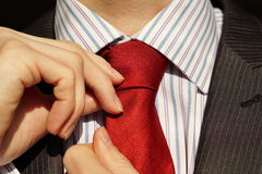 Male hands adjusting a red tie around a neck of a young male in a business suit royalty free stock photos