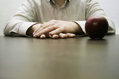 Male hands and an apple. Male hands on a brown table and an apple Stock Photography