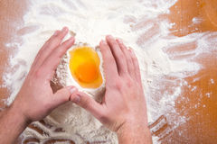 Male hands around broken egg on flour Royalty Free Stock Photography
