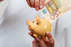 Male hands with banknote and piggybank Royalty Free Stock Photo