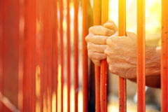 Male hands behind prison yard bars. Incarcerated captivated person in jail Royalty Free Stock Photo
