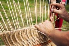 Male hands braiding wicker basket. Hands of man braiding wicker basket Royalty Free Stock Images