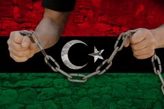 Male hands break the iron chain, symbol of tyranny, protest against the background of the national flag of Libya, the concept of