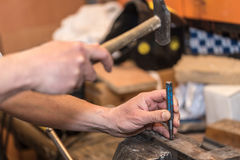 Male hands of builder man holding hammer and scored. Closeup photo Royalty Free Stock Image