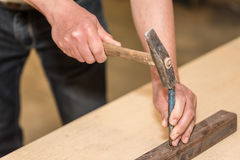 Male hands of builder man holding hammer and scored. Closeup photo Royalty Free Stock Photos