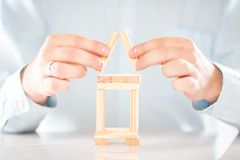 Male hands building a house from wooden blocks. Business, happy life, house or mortgage concept royalty free stock images