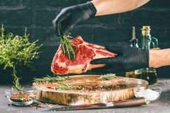Male hands of butcher or cook holding tomahawk beef steak on dark rustic kitchen table background stock photography