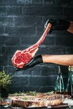 Male hands of butcher or cook holding tomahawk beef steak on dark rustic kitchen table background stock photos